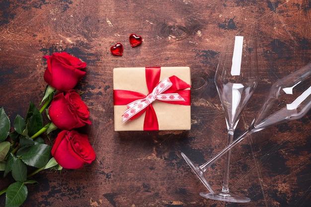 Buquê de flores rosas vermelhas, caixa de presente e taças de champanhe em fundo de madeira