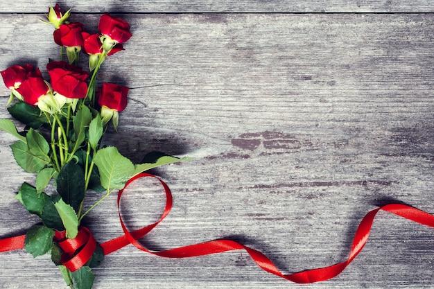 Buquê de flores rosas vermelhas com fita vermelha
