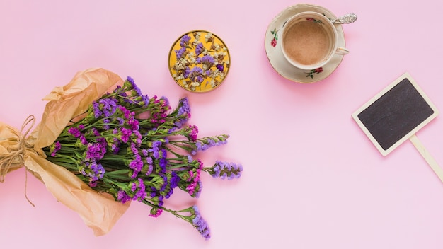 Buquê de flores roxas; montanha russa; xícara de café; e rótulo de cartaz no fundo rosa
