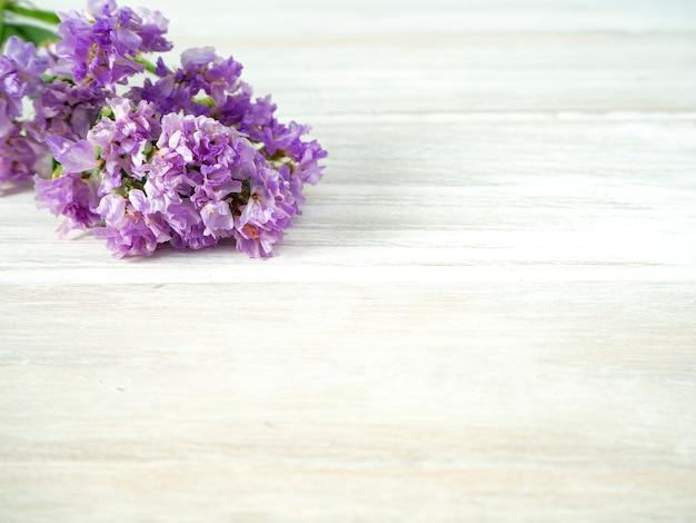 Buquê de flores roxas statice sobre uma mesa de madeira branca