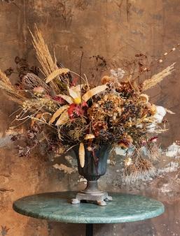 Buquê de flores secas em um vaso perto de uma parede marrom grunge