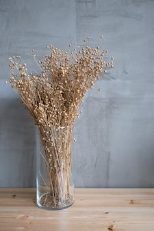 Buquê de flores secas em um vaso transparente sobre uma mesa de madeira.