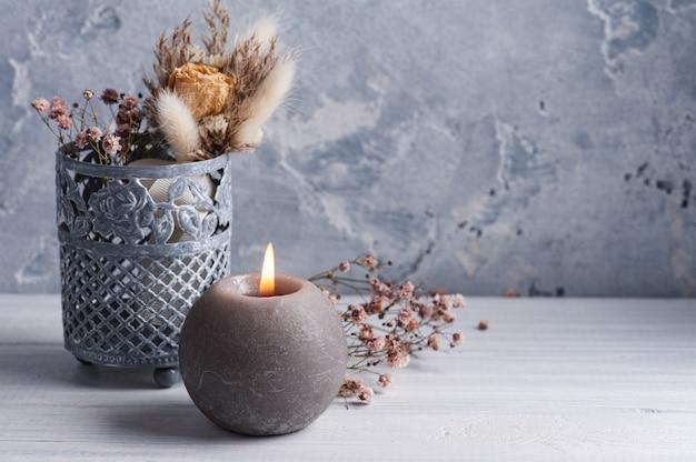 Buquê de flores secas em vaso de lata na mesa de madeira branca, vela acesa. copie o espaço para texto, para saudação, convite