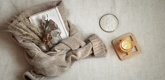 Buquê de flores secas no suéter pastel quente e vista superior da vela, conceito de conforto de outono