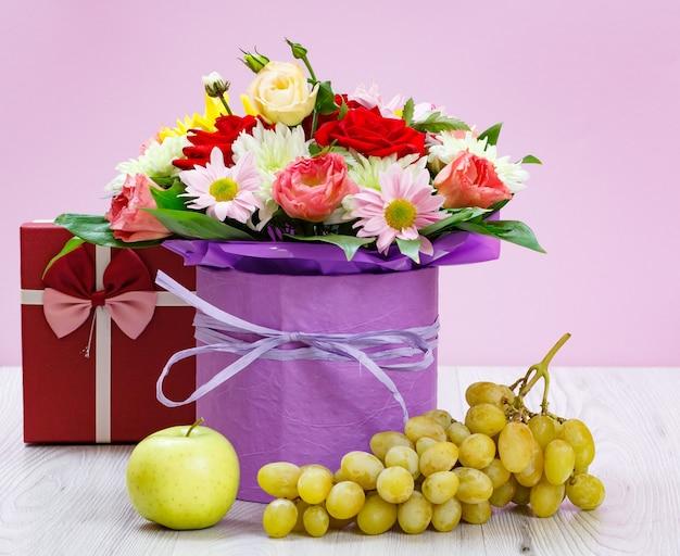 Buquê de flores silvestres, caixa de presente, uvas e uma maçã nas tábuas de madeira