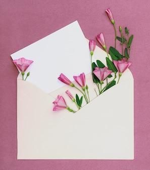 Buquê de flores silvestres cor de rosa em um envelope cartão com lugar para design