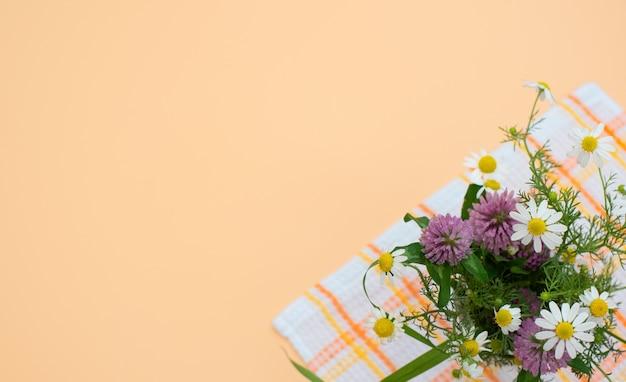 Buquê de flores silvestres de trevo e camomila close-up na toalha contra um fundo de pêssego.