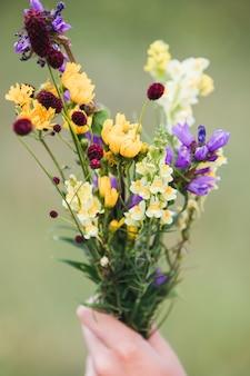 Buquê de flores silvestres mistas em uma mão.