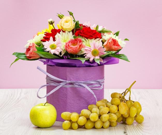 Buquê de flores silvestres, uvas e uma maçã nas placas de madeira.