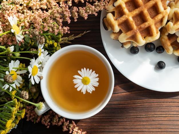 Buquê de flores, sobremesa em um prato branco, uma xícara de chá