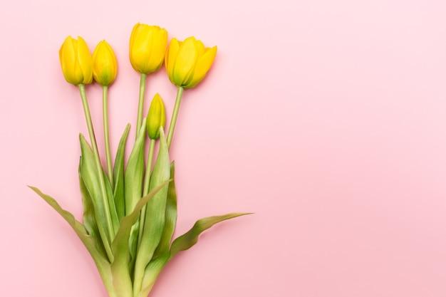 Buquê de flores tulipa amarela em fundo rosa. vista plana, vista superior