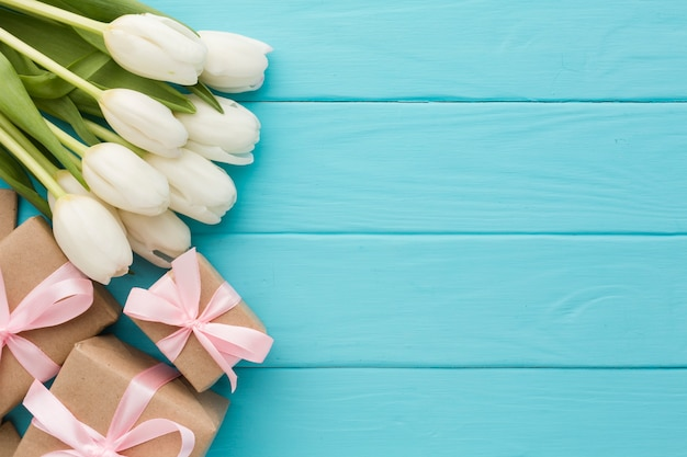 Buquê de flores tulipa com presentes em fundo de madeira
