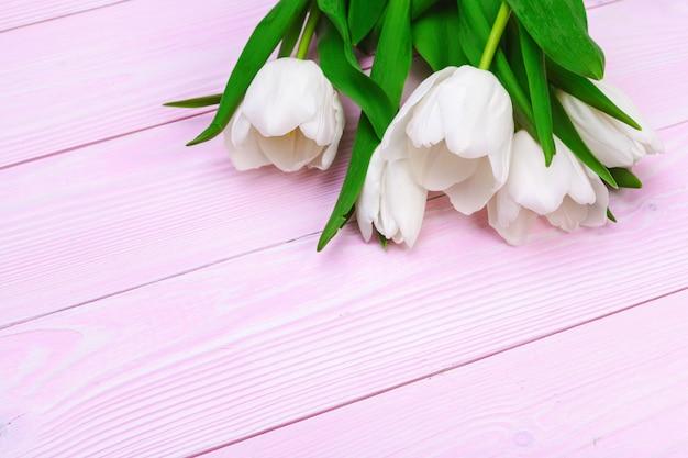 Buquê de flores tulipa em fundo rosa de madeira com espaço de cópia