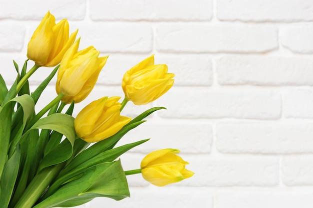 Buquê de flores tulipa na parede de tijolo decorativo branco. fundo florido natural com tulipa de flor amarela de primavera.