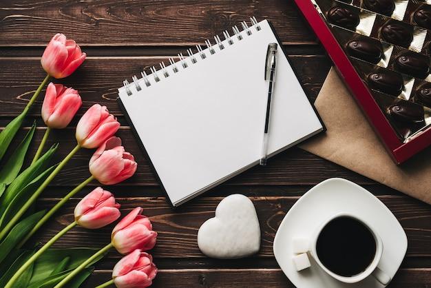 Buquê de flores tulipa rosa e uma xícara de café com uma caixa de chocolates doces na mesa de madeira