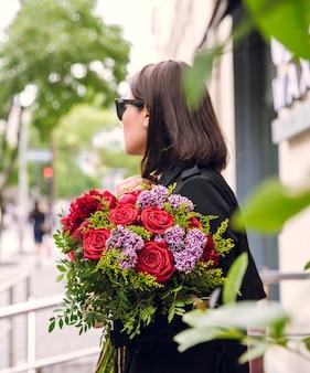 Buquê de flores variuos nas mãos da menina