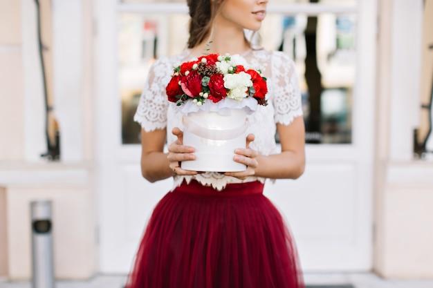 Buquê de flores vermelhas e brancas nas mãos de uma menina bonita com saia de tule marsala na rua
