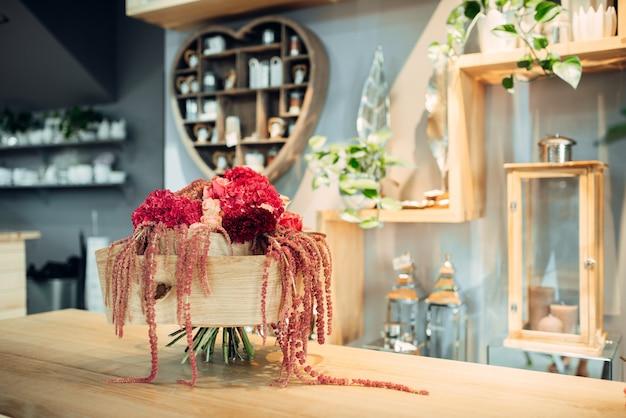 Buquê de flores vermelhas frescas com decoração na mesa da loja