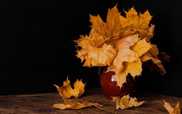 Buquê de folhas caídas de outono em um vaso de barro. ainda vida em fundo escuro.