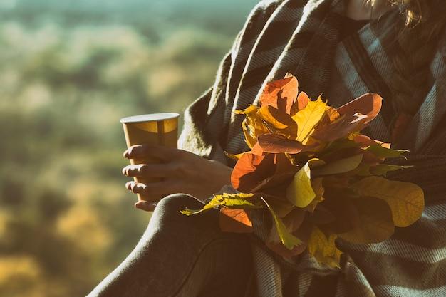 Buquê de folhas de outono e copo de papel em uma mão feminina. fechar-se