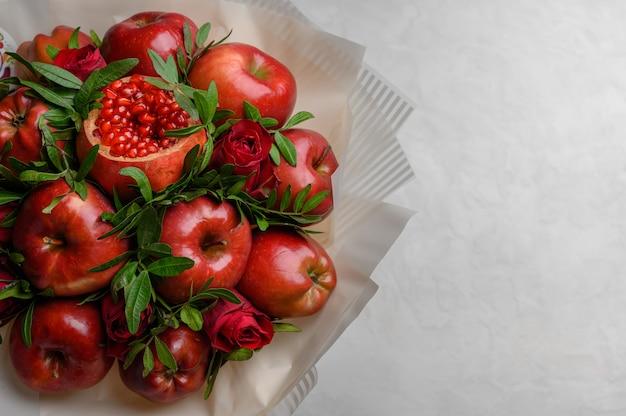 Buquê de frutas de maçãs, romã e rosas em um fundo branco