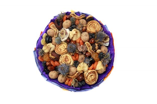 Buquê de frutas secas com espinhos azuis embrulhados em papel azul, vista superior