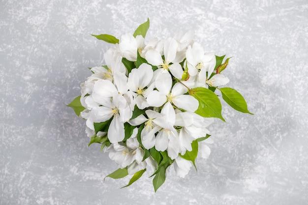 Buquê de galhos de macieira branca florescendo em pano de fundo cinza claro texturizado.