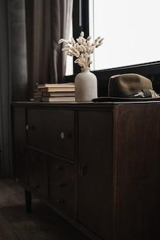 Buquê de grama de cauda de coelho coelho na panela, pilha de livros, chapéu na mesa contra a janela