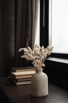 Buquê de grama de cauda de coelho de coelho, livros empilhados na mesa de madeira sólida contra a janela.