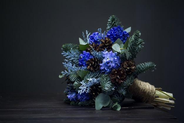 Buquê de inverno de galhos de pinheiro, jacintos azuis e cones