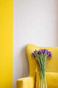 Buquê de íris azuis em fundo de cadeira amarela. aniversário, dia da mulher, 8 de março, conceito de amor e congratulações. com espaço de cópia para texto vertical