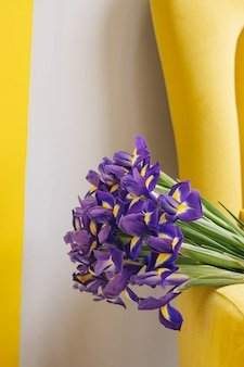 Buquê de íris em cadeira amarela em fundo cinza feriado dia das mães dia das mulheres fundo cópia espaço