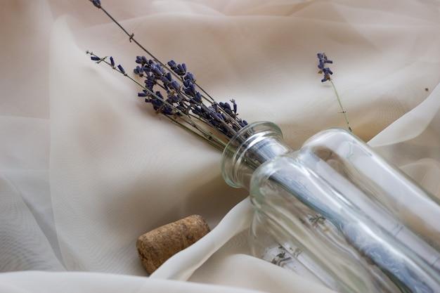 Buquê de lavanda em uma garrafa de vidro ou vaso em um fundo claro, vista superior