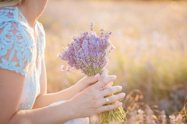 Buquê de lavanda nas mãos de uma jovem mulher sentada em um campo de verão