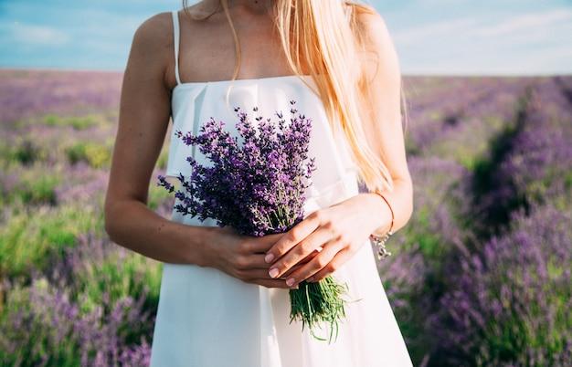 Buquê de lavanda nas mãos de uma mulher em um vestido branco