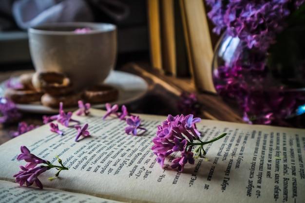 Buquê de lilases e uma xícara de chá branca em um fundo de madeira