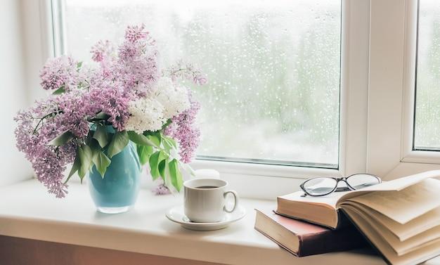 Buquê de lilases em um vaso, xícara de café e livros no parapeito da janela.
