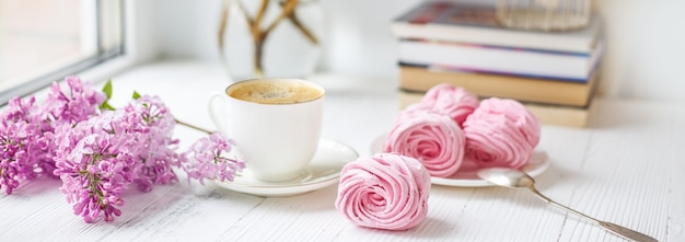 Buquê de lilases, xícara de café, marshmallow caseiro e pilha de livros no peitoril da janela
