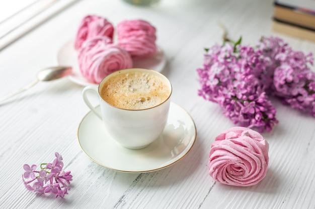 Buquê de lilases, xícara de café, marshmallow caseiro. manhã de primavera romântica