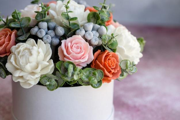 Buquê de lindas flores rosas brilhantes em uma caixa de papelão cilíndrica para presente