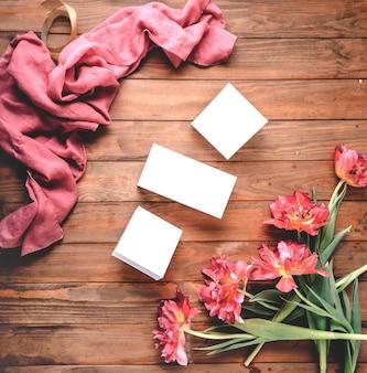 Buquê de lindas tulipas e caixas brancas em uma mesa de madeira tulipa encaracolada lenço rosa leve