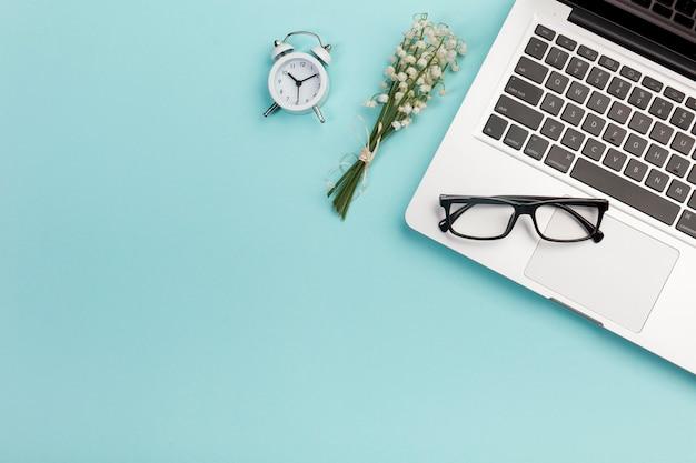 Buquê de lírio do vale com despertador, óculos e laptop na mesa de escritório azul