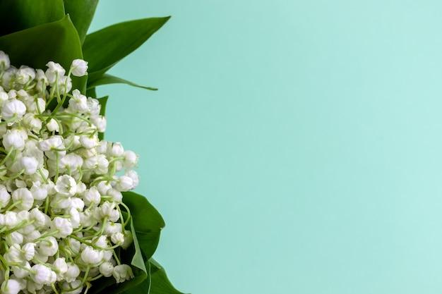 Buquê de lírios brancos do vale em folhas verdes sobre um fundo de hortelã com espaço de cópia. foco seletivo. vista de perto