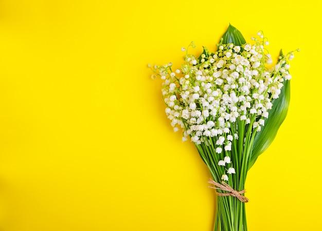 Buquê de lírios brancos do vale em um fundo amarelo