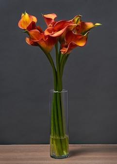 Buquê de lírios de calla amarelos e vermelhos em um vaso na mesa em fundo escuro.