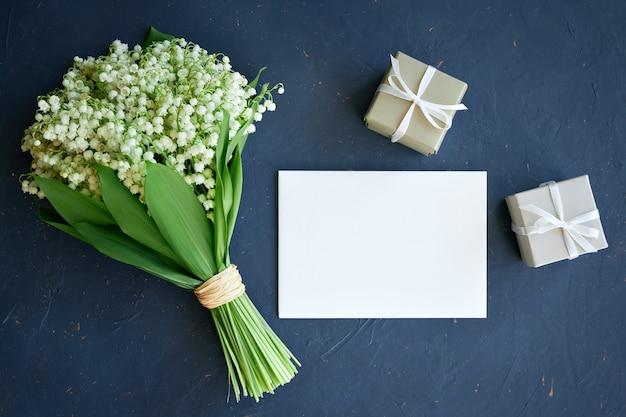 Buquê de lírios do vale, cartão postal, caixas de presente em um fundo azul escuro
