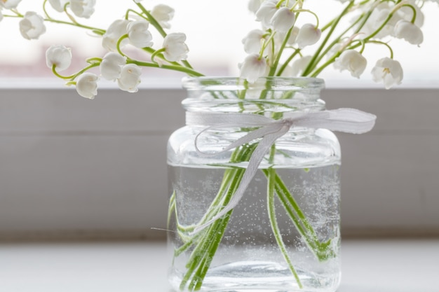 Buquê de lírios do vale é em um vaso de vidro simples em uma superfície de madeira
