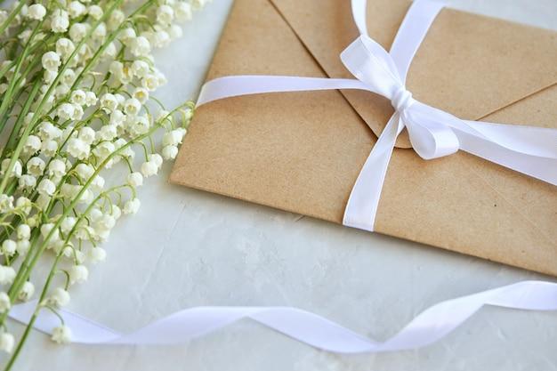 Buquê de lírios do vale, envelope artesanal com um laço em um fundo azul