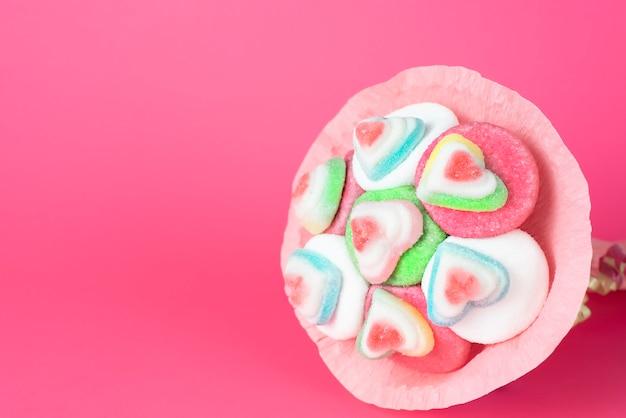 Buquê de marmelada e doces em embalagem rosa em um fundo rosa