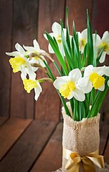 Buquê de narcisos amarelos close-up em uma mesa de madeira rústica